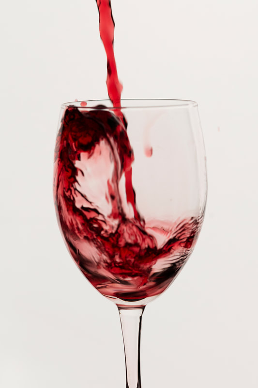 Red wine being poured into a wine glass.